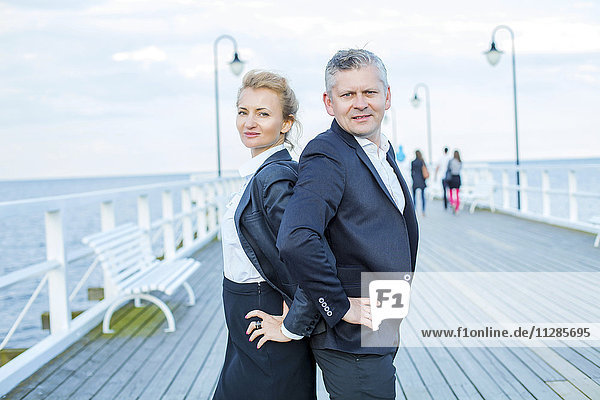 Two business people on jetty with hands on hips