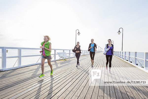 Group of women in sports clothing running on jetty
