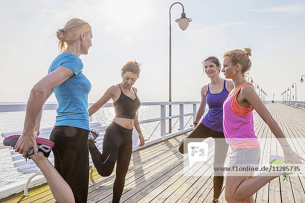 Group of women stretching legs on jetty