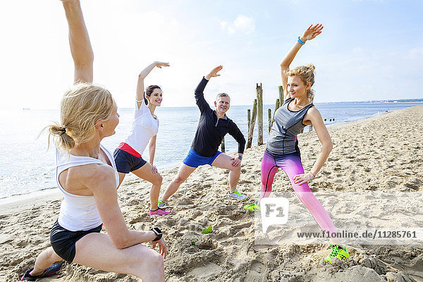 Group of friends stretching on beach
