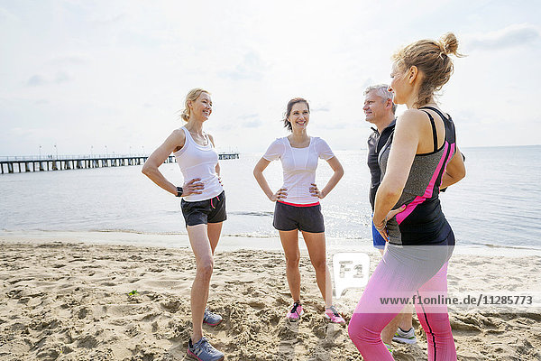 Group of runners on beach taking a break