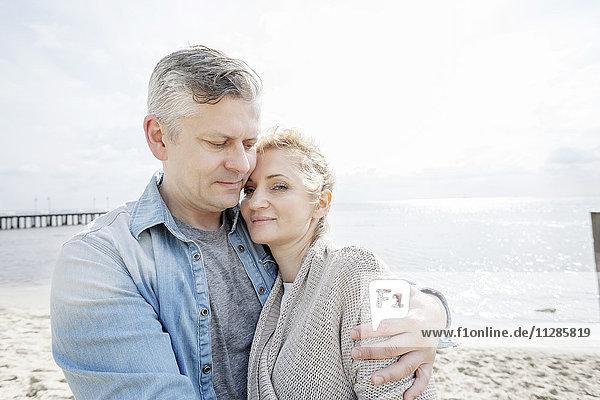 Man on beach embracing girlfriend
