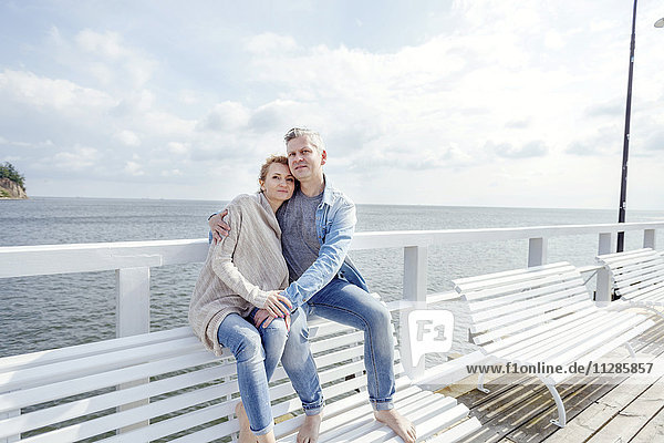 Couple in love sitting on jetty