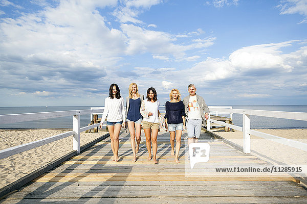 Group of friends take a walk along the beach
