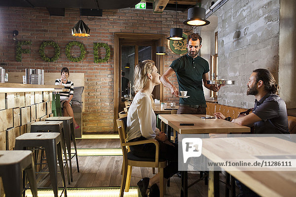 Waiter serving espresso to guests in restaurant