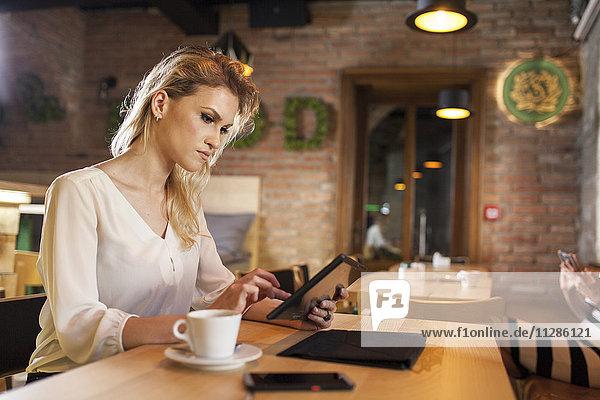 Woman in coffee shop using digital tablet