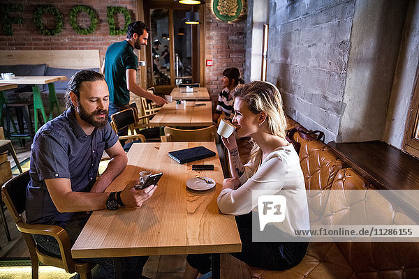 Woman drinking espresso while man is using phone