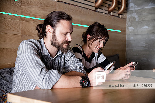 Couple in coffee shop looking at their smartphones