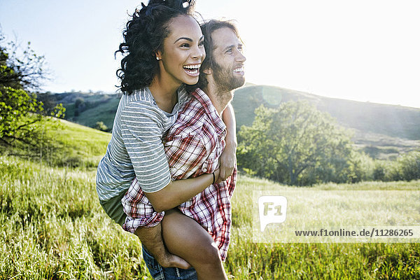 Smiling Man carrying girlfriend piggyback on hill