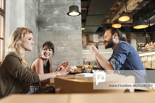 Group of friends in coffee shop eating snacks