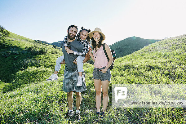 Portrait of happy family standing on hill