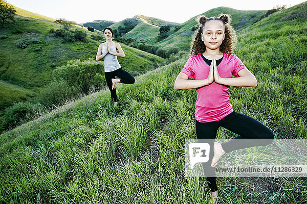 Mother and daughter practicing yoga on hill Mother and daughter practicing yoga on hill