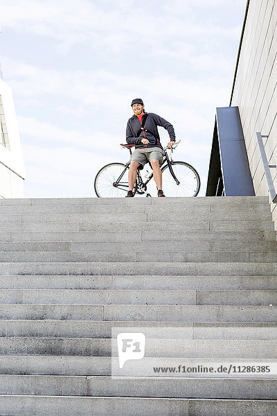 Bike messenger resting on stairway