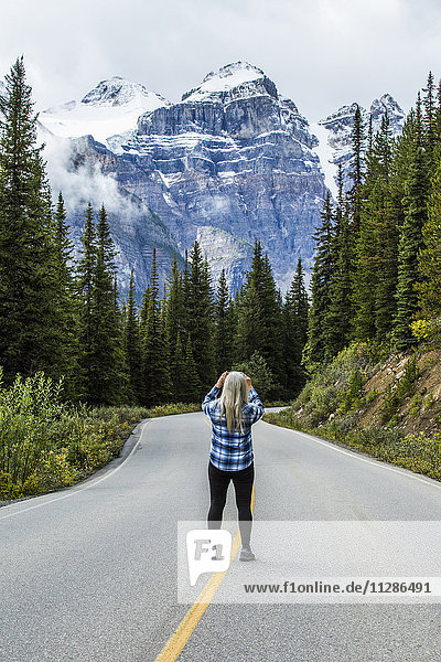 Caucasian woman standing in road photographing mountain