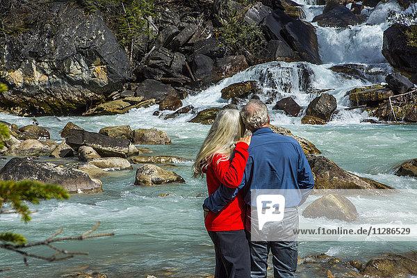 Caucasian couple admiring rapids over rocks