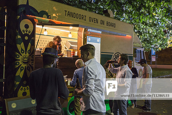 Group of customers at food truck at night
