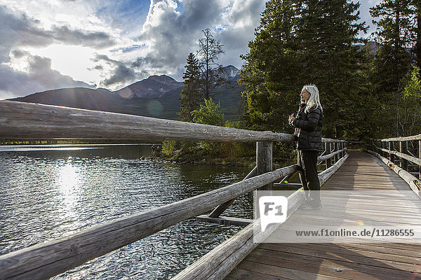 Caucasian woman holding binoculars at mountain lake