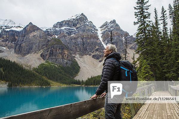 Caucasian man standing on boardwalk admiring mountain