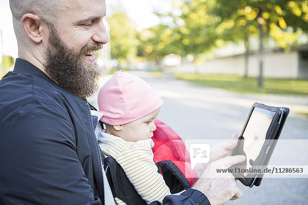 Father with baby girl in baby carrier using digital tablet
