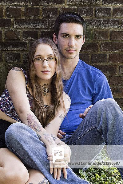 Caucasian couple sitting on ground leaning on wall