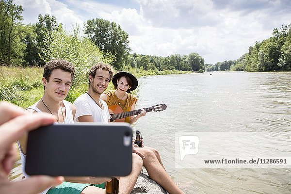 Group of friends relaxing on the riverbank