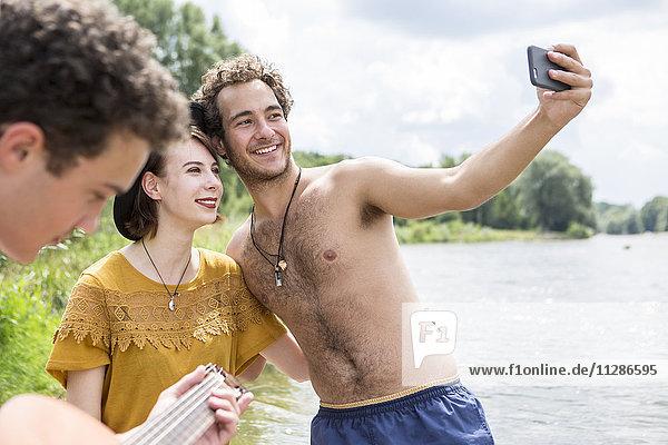 Friends taking selfie on the riverbank