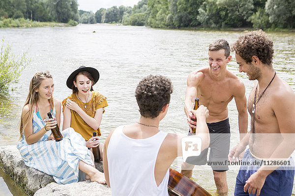 Group of friends drinking beer on the riverbank
