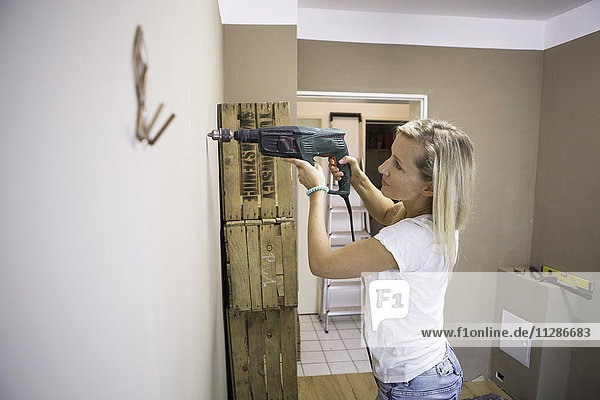Woman using drill to fix coat hook in apartment