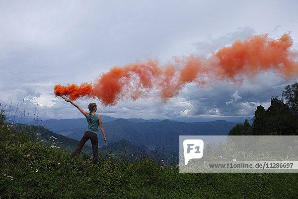 Caucasian girl holding orange smoke flare on mountain range