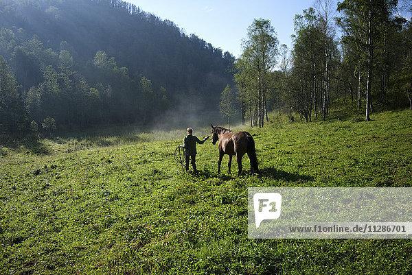 Caucasian girl walking horse in field