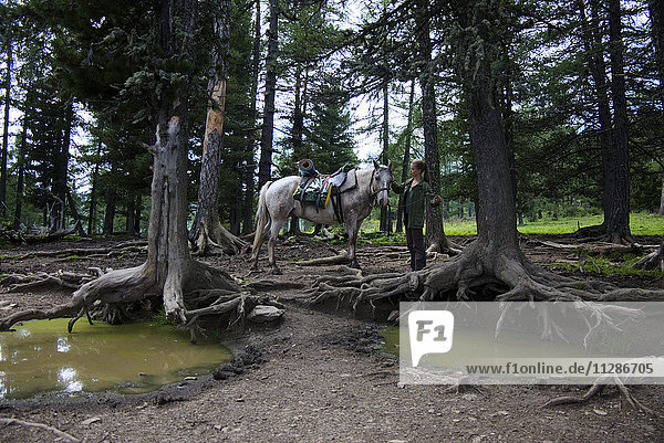Caucasian girl petting horse in forest near puddles Caucasian girl petting horse in forest near puddles