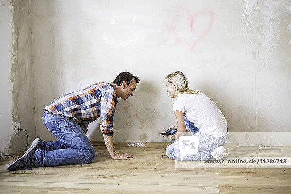 Young couple laying parquet in apartment