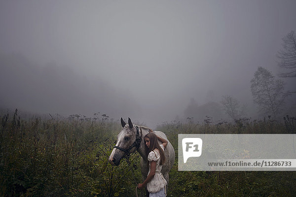 Caucasian girl petting horse in foggy field