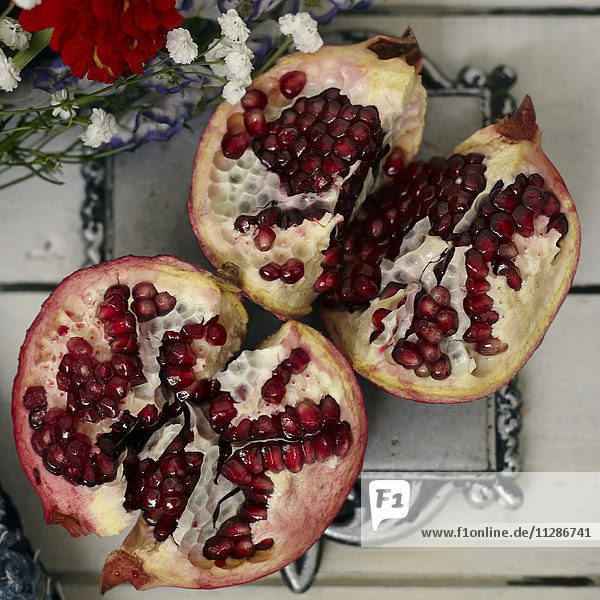 Red seeds in sliced pomegranate near flowers