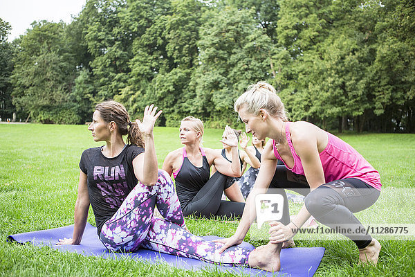 Young woman teaches yoga class in park