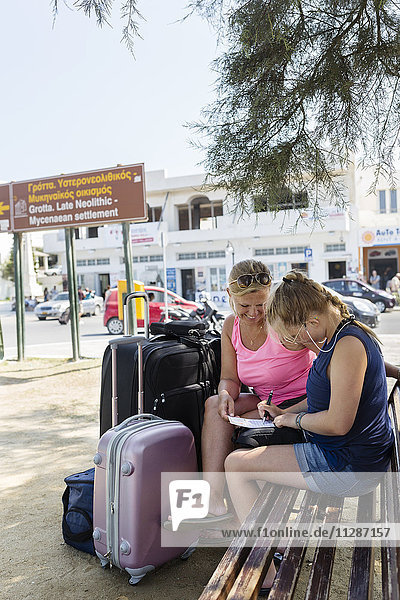 Women sitting on bench with suitcases