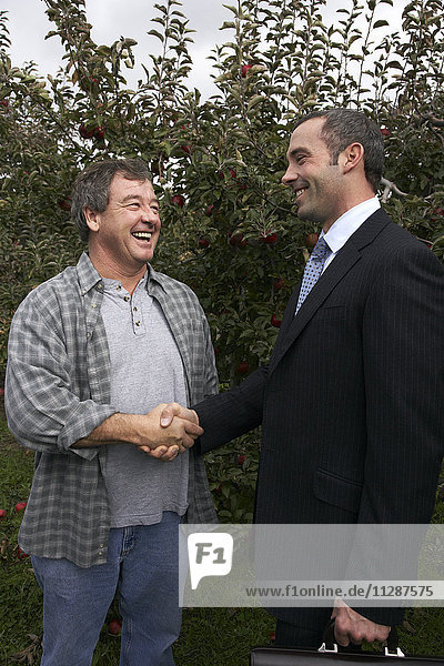 Businessman and Farmer in Orchard