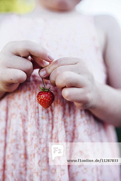 Girl holding strawberry