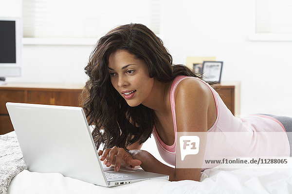 Woman Using Laptop on Bed