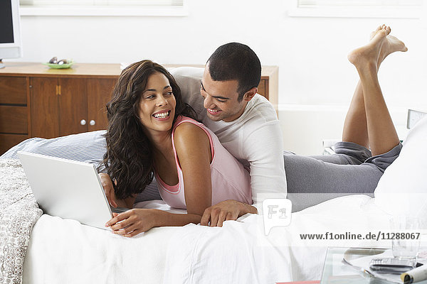 Couple with Laptop on Bed