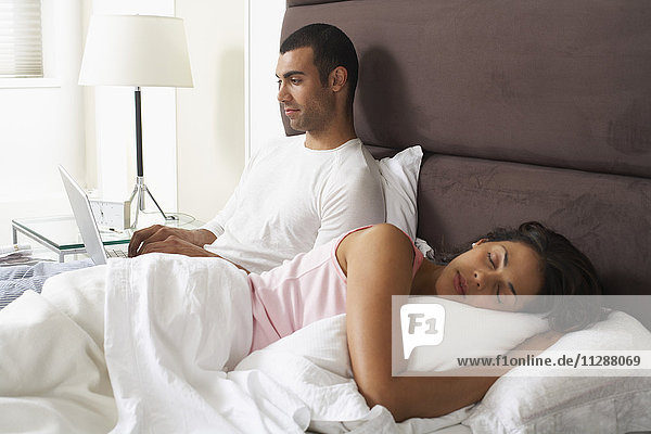 Couple in Bed  Man Using Laptop