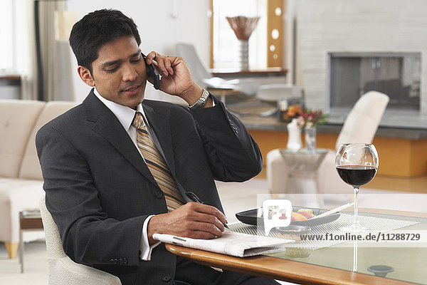 Man Using Cellular Phone at Dinner Table