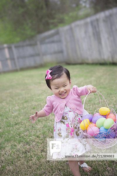 Toddler Girl Running and Smiling with Full Easter Egg Bakset