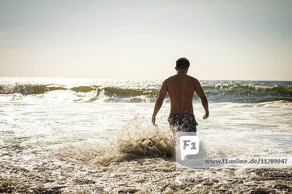 Mexiko  Nuevo Vallarta  Riviera Nayarit  junger Mann  der in den Ozean eintritt.