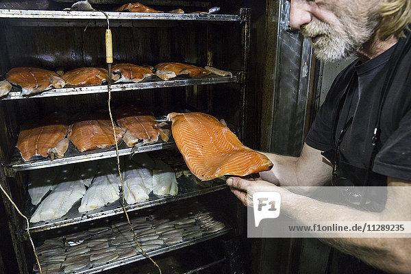 Mann betrachtet frisch geräuchertes Lachssteak in einer Räucherei
