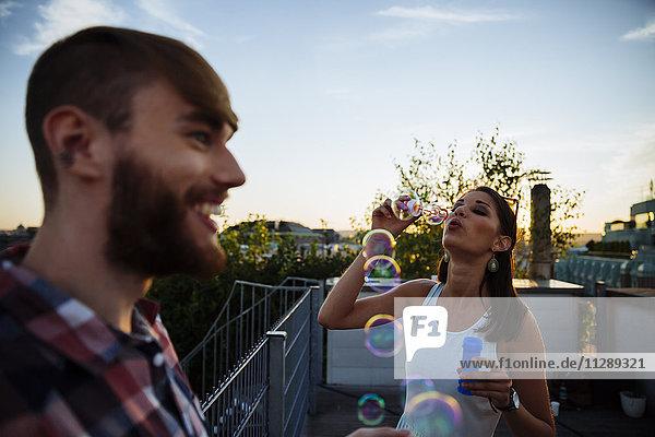 Junge Frau bläst Seifenblasen auf der Dachterrasse Junge Frau bläst Seifenblasen auf der Dachterrasse