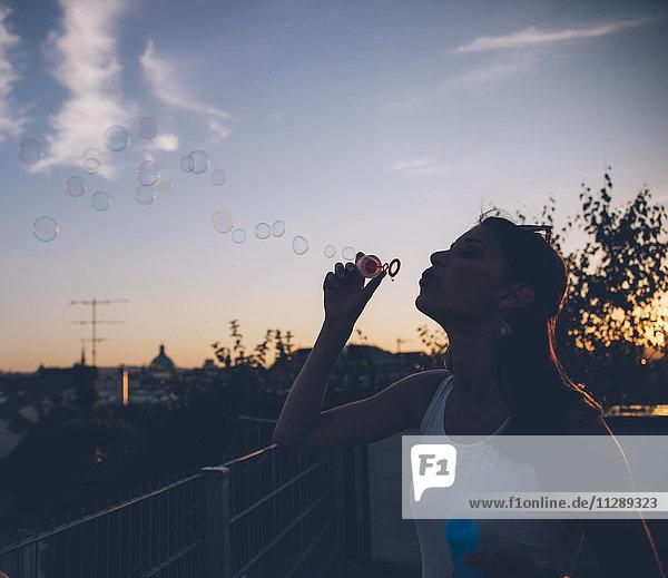 Junge Frau bläst Seifenblasen auf der Dachterrasse in der Abenddämmerung