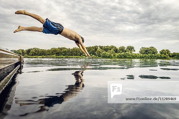 Mann springt vom Steg ins Wasser