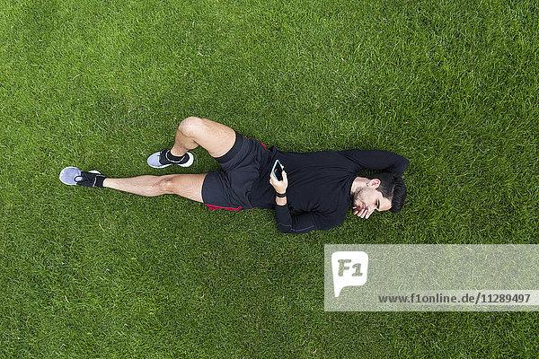 Jogger im Gras liegend mit Smartphone