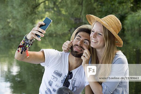 Verspieltes junges Paar am See mit einem Selfie